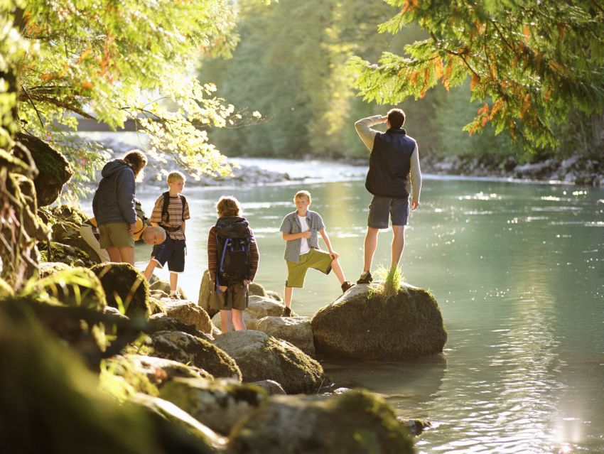 Family on hike, standing on rocks next to river