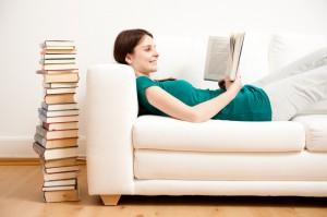 Junge Frau liest auf Sofa Buch